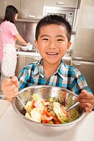 Chinese boy tossing salad in kitchen