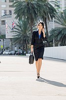 Hispanic businesswoman walking and talking on cell phone