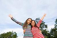 Smiling girls hugging outdoors