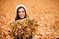 Caucasian woman playing in autumn leaves