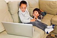 Two young boys using a lap top together inside.