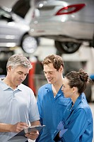 Mechanics talking in auto repair shop
