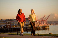 Two Women, one Caucasian, one Asain, walking along Elliot Bay, in Seattle, WA.