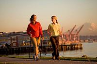 Two Women, one Caucasian, one Asain, walking along Elliot Bay, in Seattle, WA.