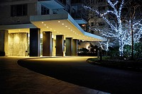 Apartment Building Driveway at Night, Decorated with White Lights in Trees for the Christmas Holiday Season