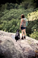 A female hiker and her dog look out over dense forest from a clifftop viewpoint.