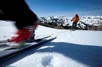Low angle perspective of a skier´s boot motion blurred with a skier int he background.