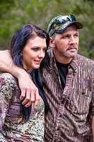 Two hunters portrait, father and daughter in camouflage outfit, male Caucausian, 40 years old, female Caucasian with long black hair, 18 years old, Te...