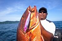 Man holding fresh caught cubera snapper lutjanus cyanopterus, panama