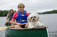 Two Girls In A Canoe With Their Pet Dog, Lake Of The Woods Ontario Canada