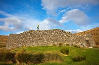 A Woman Standing On Top Of A Stone Wall At Staigue Fort, Near Castlecove, County Kerry, Ireland