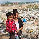 A Girl Holds Her Young Brother While Standing In A Garbage Dump, Guatemala City Guatemala