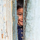 A Boy Peaking Through A Crack In The Door, Guatemala City Guatemala