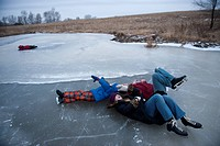 Children take break from ice skating on a small pond near Dunbar, NE.