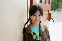 Pretty, Asian, elementary student at school doorwary.