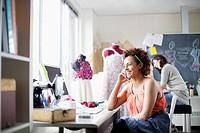 Fashion designer talking on smart phone in studio.