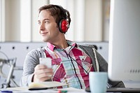 Male, creative professional listening to music