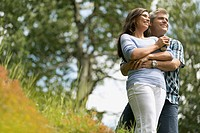 Attractive couple hugging in meadow.