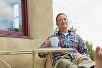 Middle_aged man relaxing with a coffee outdoors
