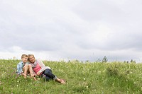 Grandmother and grandson relaxing in meadow