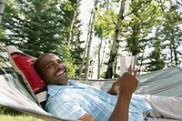 African American man relaxing with book in hammock