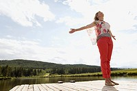Mature woman with arms outstretched on boat dock