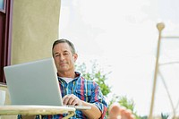 Middle_aged man using laptop outdoors