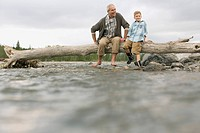 Grandfather and grandson sitting on log over water
