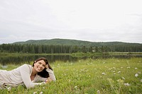 Pretty, mid_adult woman lying in meadow