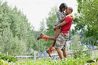 Mid-adult man hugging and lifting woman in their outdoor garden (thumbnail)