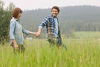 Middle_aged couple walking in high grass holding hands