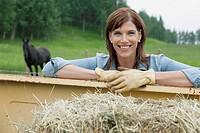 Pretty woman leaning on truck on rural property