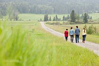 Family of four walking on road along rural property
