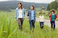 Family of four walking in field on rural property