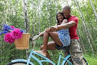 African_American couple cuddling on bicycle