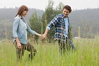 MIddle_aged couple holding hands while walking in field
