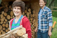 Youth getting logs from the woodpile with his dad