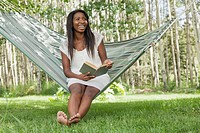 Young adult woman sitting in hammock with book