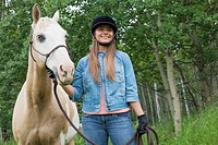 Teenage girl holding horse by reins.