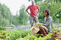 Young African_American couple working in vegetable garden.