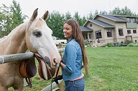 Young woman with horse on rural property
