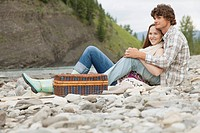 Young couple relaxing by a stream with picnic basket
