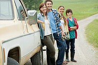 Rural family of four standing by work truck