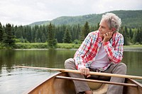 Senior man contemplating while sitting in canoe