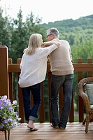 View from behind of middle_aged couple on outdoor deck