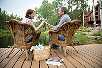 Middle_aged couple toasting with wine on dock