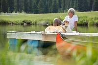 Senior man and his dog relaxing on dock