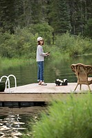 Pretty, middle_aged woman fishing off dock