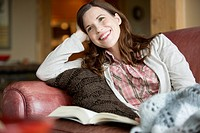 Pretty woman relaxing on couch with book (thumbnail)