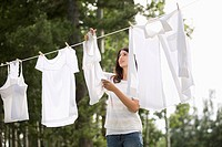 Mid_adult woman hanging clothes on outdoor clothesline